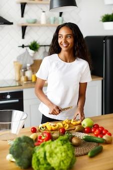 Mulher muito afro corta um pimentão amarelo e sorrindo olha pela janela