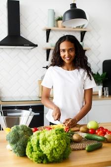 Mulher muito afro está cortando um pimentão amarelo e sorrindo