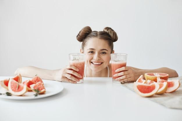 Mulher muito alegre com bolos sorrindo sentado à mesa com fatias de toranja saudável desintoxicação dieta batido sobre parede branca.