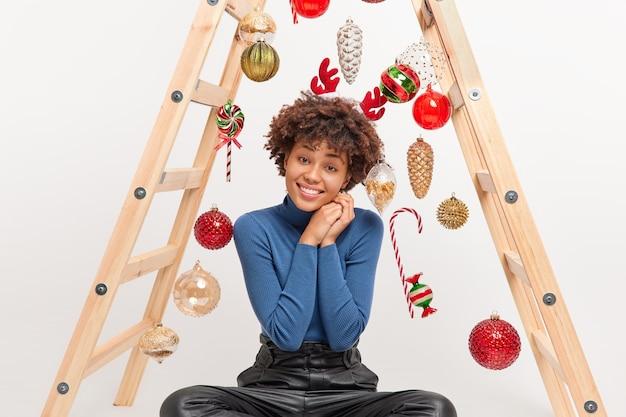 Mulher muito alegre com cabelo encaracolado inclina a cabeça e sorri alegremente vestida com roupas casuais posa no chão com escada para decorar o quarto indo para comemorar o ano novo passa o tempo de lazer em casa