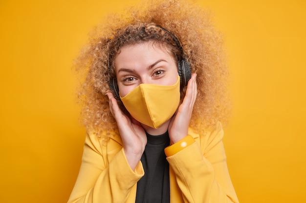Mulher muito alegre com cabelo loiro cacheado usa máscara protetora em lugar público durante a quarentena ouve música por meio de poses de fones de ouvido sem fio contra a parede amarela. conceito de cuidados de saúde.