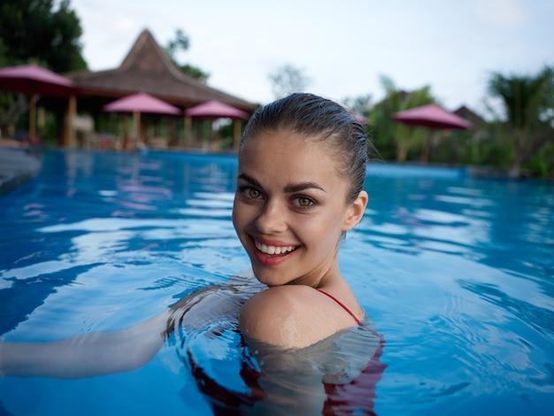 Mulher muito alegre nadando na piscina de férias de luxo na ilha de bali