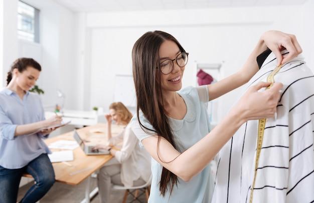 Mulher muito alegre segurando uma fita métrica e calculando o comprimento dos ombros do cardigã enquanto seus colegas trabalham ao fundo