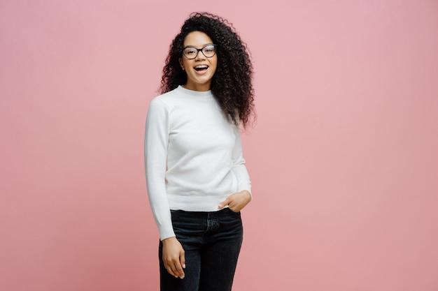 Mulher muito alegre vai trabalhar, ri de algo positivo, usa jeans e jumper branco puro