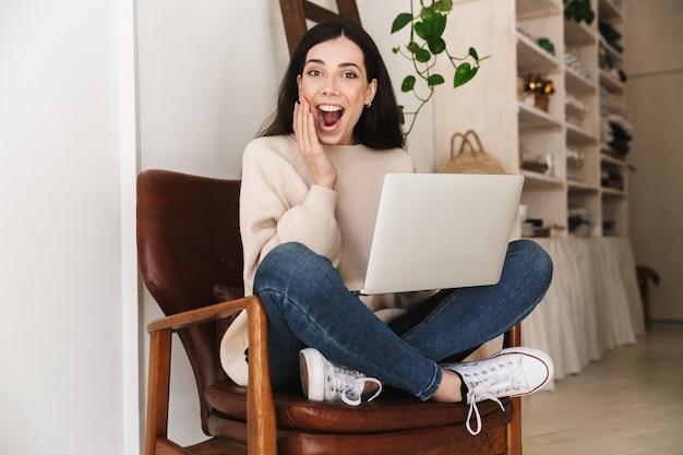 Mulher muito animada, descansando em um apartamento e trabalhando em um laptop enquanto está sentado na cadeira