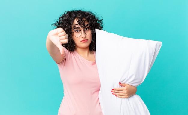 Mulher muito árabe se sentindo mal, mostrando os polegares para baixo. vestindo pijama e segurando um travesseiro