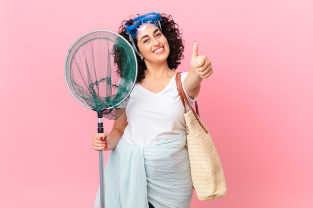 Mulher muito árabe se sentindo orgulhosa, sorrindo positivamente com o polegar para cima com óculos de proteção. conceito de pescador