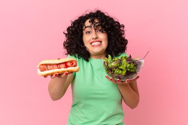 Mulher muito árabe segurando uma salada e um cachorro-quente. conceito de dieta