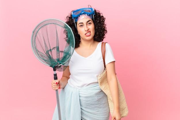 Mulher muito árabe sentindo-se perplexa e confusa com os óculos de proteção. conceito de pescador