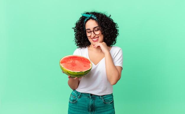 Mulher muito árabe, sorrindo com uma expressão feliz e confiante com a mão no queixo e segurando uma melancia. conceito de verão