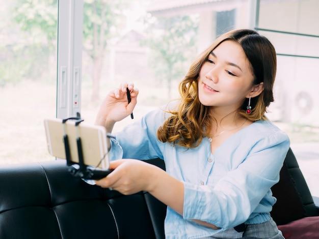 Mulher muito asiática é o blogueiro online para rever o produto