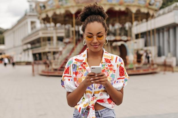 Mulher muito atraente em calças jeans, camisa brilhante colorida e óculos de sol laranja segurando o telefone e mandando mensagens do lado de fora
