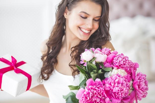 Mulher muito bonita com flores e presentes dentro de casa