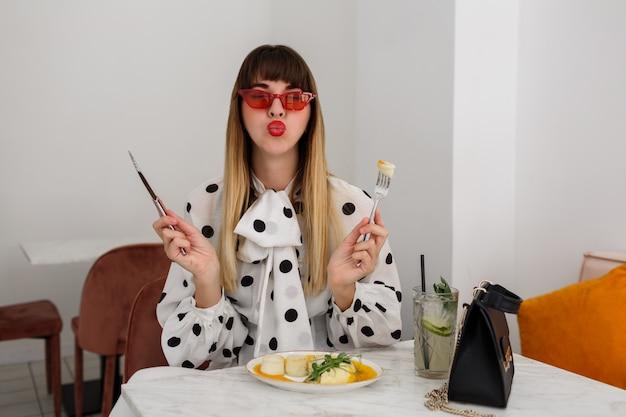 Mulher muito bonita, desfrutando de seu café da manhã saudável no café moderno e elegante