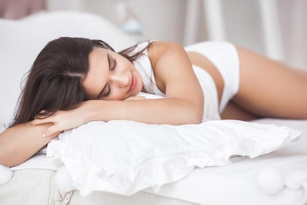 Mulher muito bonita na cama. retrato de uma jovem atraente no quarto