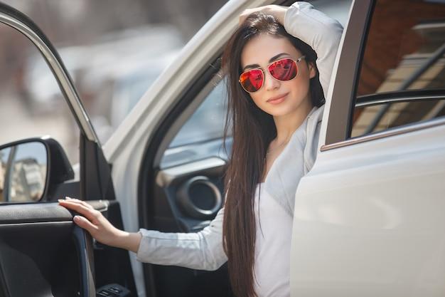 Mulher muito bonita no carro segurando flores
