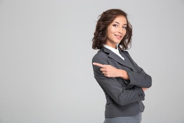 Mulher muito cacheada e sorridente feliz com uma jaqueta cinza cruzada de braços e apontando para longe na copyspace