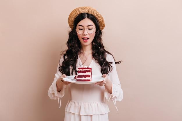 Mulher muito chinesa em copos, segurando o prato com sobremesa. mulher atraente encaracolada asiática olhando para o bolo.