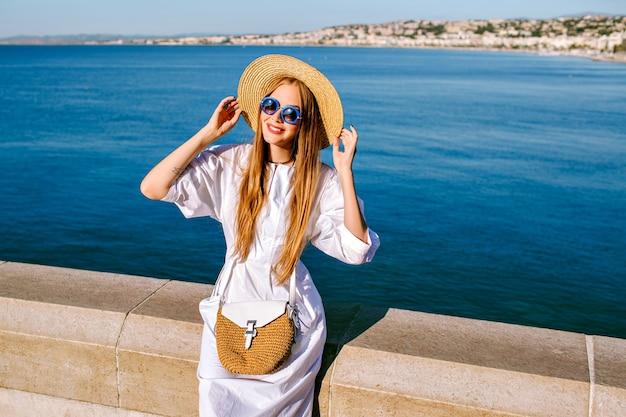 Mulher muito elegante com vestido branco, chapéu de palha e bolsa posando perto do mar