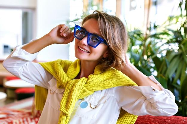 Mulher muito elegante, posando no restaurante, palmeiras ao redor, usando óculos escuros e suéter amarelo neon, look casual elegante, maquiagem natural, penteado curto.