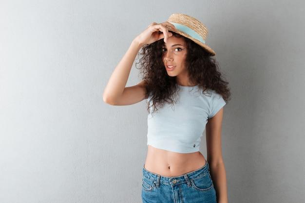 Mulher muito encaracolada no chapéu