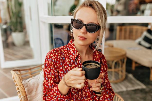 Mulher muito estilosa e elegante usando um vestido brilhante, bebendo café e descansando ao ar livre