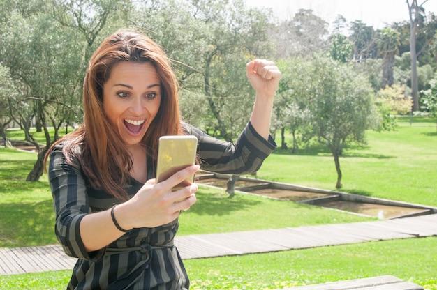 Mulher muito feliz com telefone móvel, comemorando a vitória