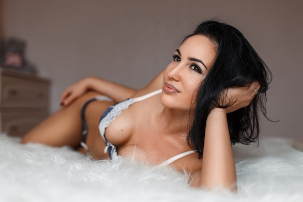 Mulher muito feliz com um corpo lindo em lingerie na cama