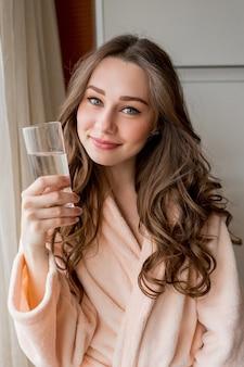 Mulher muito feliz em roupão de banho bebendo água doce em casa