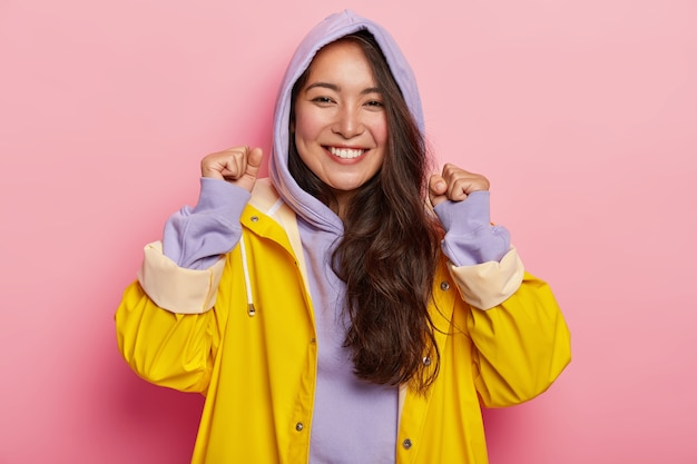 Mulher muito feliz levanta os punhos cerrados, expressa emoções positivas, tem beleza natural, vestida com roupas casuais, capa de chuva para o tempo chuvoso, sorri amplamente