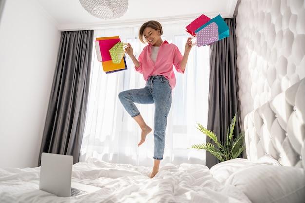 Mulher muito feliz se divertindo pulando na cama em casa com sacolas de compras coloridas