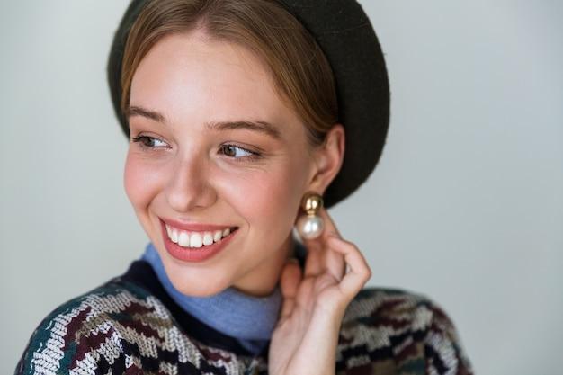 Mulher muito feliz usando brincos posando e sorrindo isolado no branco
