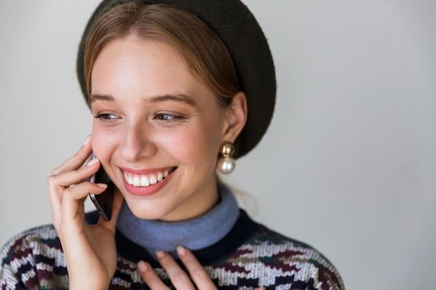Mulher muito feliz usando brincos sorrindo e falando no celular isolado no branco