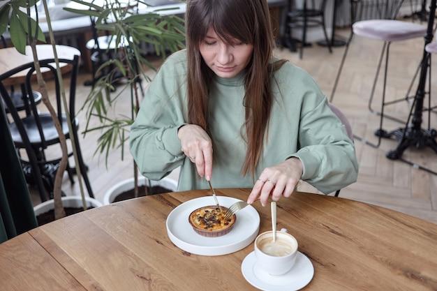 Mulher muito fofa sentada em um café vazio, comendo bolo e bebendo café