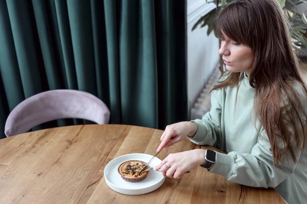 Mulher muito fofa sentada num café a comer bolo