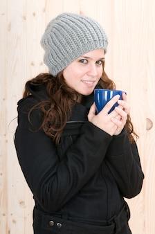 Mulher muito fria em uma cabana no outono ou inverno