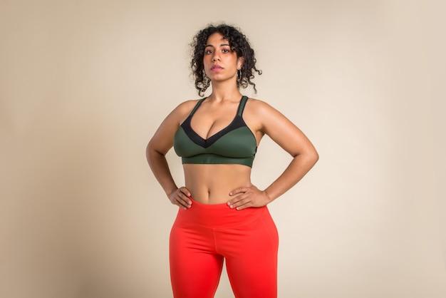 Mulher muito grande usando roupas esportivas e posando no estúdio