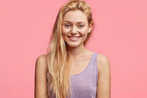 Mulher muito jovem com cabelo comprido e luxuoso e sorriso agradável, vestida com uma camiseta roxa casual, alegra-se com as boas notícias, posa contra rosa
