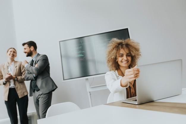 Mulher muito jovem de cabelo encaracolado trabalhando em um laptop em um escritório bem iluminado com um membro da equipe discutindo atrás dela