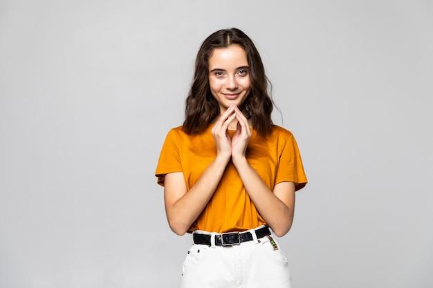 Mulher muito jovem e animada com as mãos sob o queixo, isolada contra uma parede cinza