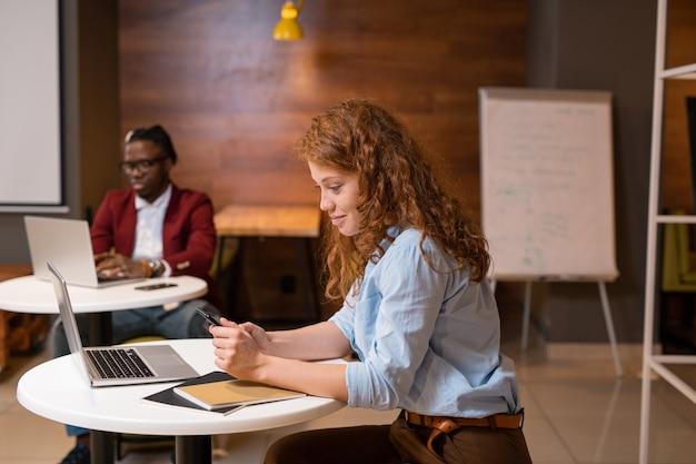 Mulher muito jovem e casual com mensagens de texto no smartphone em um café da faculdade perto da mesa