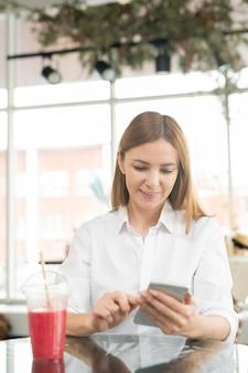 Mulher muito jovem e elegante com um smartphone sentado em frente ao café da câmera, bebendo e navegando nas mercadorias online