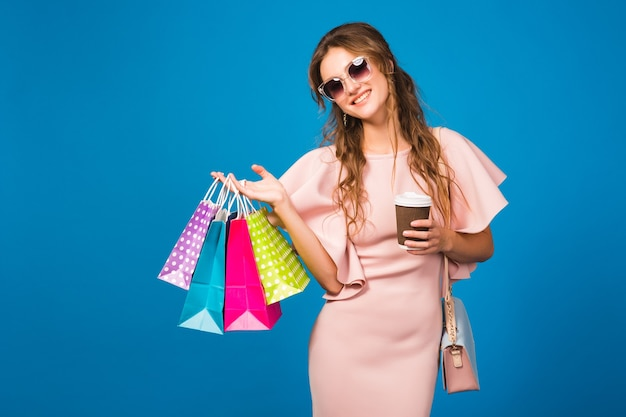 Mulher muito jovem e elegante em um vestido rosa luxuoso, bebendo café e segurando sacolas de compras