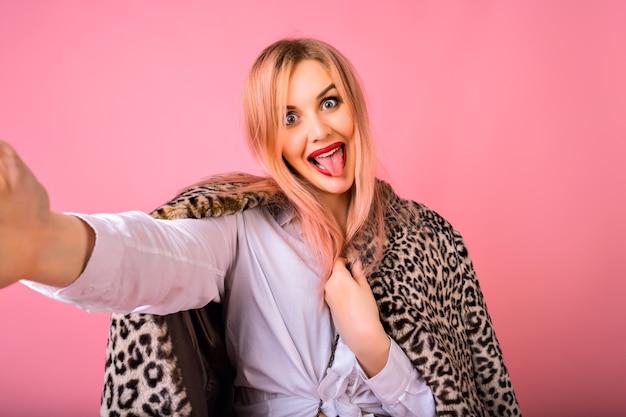 Mulher muito jovem e elegante fazendo selfie no fundo rosa, penteado da moda e maquiagem brilhante, fazendo beijo e olhando para a câmera.