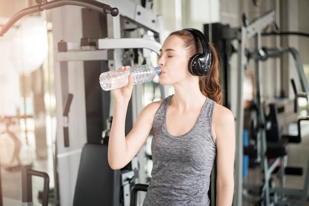 Mulher muito jovem esporte é beber água no ginásio, estilo de vida saudável