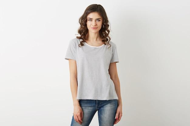 Mulher muito jovem, estilo hippie, vestida de jeans, camiseta, isolada no fundo branco, cabelos cacheados