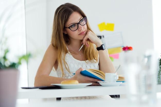 Mulher muito jovem lendo um livro e tomando café da manhã em casa.