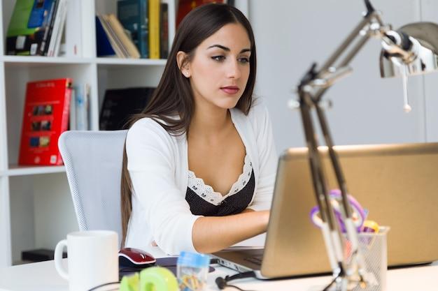 Mulher muito jovem trabalhando com laptop em seu escritório.