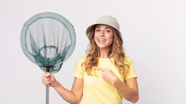 Mulher muito magra, animada e surpresa, apontando para o lado com um chapéu e segurando uma rede de pesca