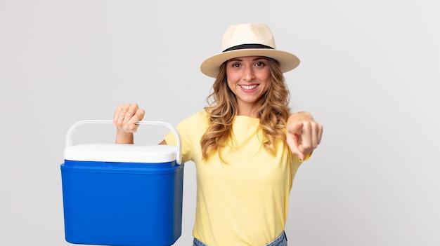 Mulher muito magra apontando para a câmera escolhendo você e segurando uma geladeira de piquenique de verão